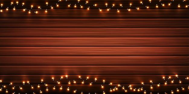Luci di natale. ghirlande d'ardore di natale di lampadine a led su fondo di legno Vettore Premium