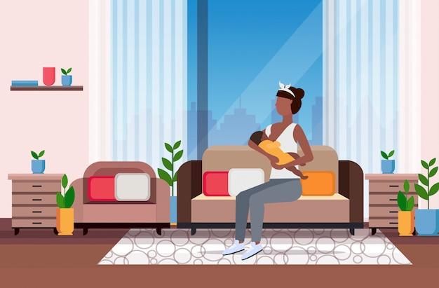 Madre l'allattamento al seno il suo neonato donna seduta sul divano con il bambino piccolo maternità nutrizione concetto di lattazione moderno salotto interno a figura intera Vettore Premium