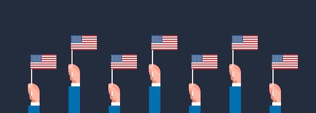 Mani che tengono la bandiera delle bandiere americane Vettore Premium