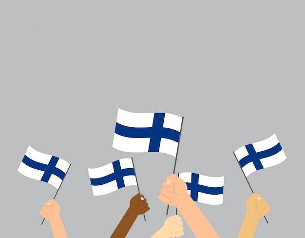 Mani che tengono le bandiere della finlandia Vettore Premium