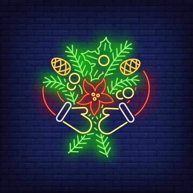 Mani in guanti che abbracciano i ramoscelli di abete con coni in stile neon Vettore gratuito