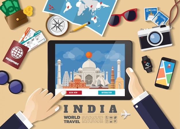 Mano che tiene destinazione di viaggio prenotazione smart tablet. luoghi famosi india. banner di concetto di vettore in stile piano con l'insieme di viaggiare oggetti, accessori e icona del turismo. Vettore Premium