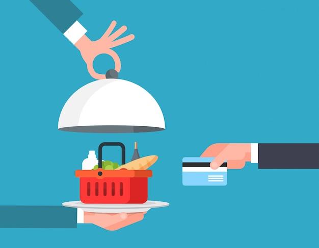 Mano di concetto di servizio di ordine e di consegna degli alimenti online che paga il canestro dei prodotti della drogheria con la carta di credito Vettore Premium