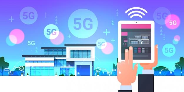 Mano umana utilizzando la tavoletta digitale online mobile app smart home system control 5g comunicazione wireless online moderna automazione della casa concetto orizzontale Vettore Premium