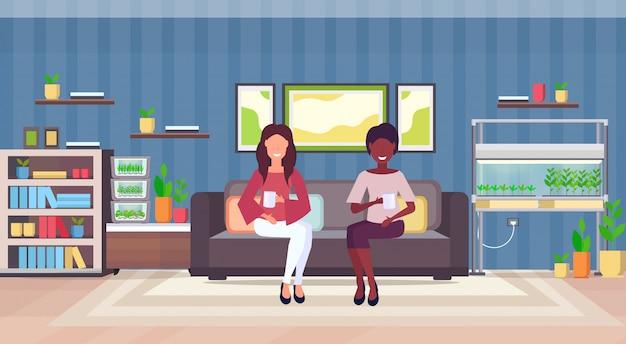 Mescolano le donne della corsa che si siedono sulle coppie dello strato che bevono l'interno moderno del salone dell'appartamento del caffè bevente con le piante della casa del contenitore di vetro elettronico domestico del terrario che coltivano il concetto orizzontale piano Vettore Premium