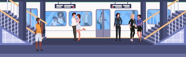 Mescoli i passeggeri della corsa alle donne degli uomini della stazione della metropolitana della metropolitana della metropolitana che stanno sull'illustrazione integrale integrale orizzontale piana di vettore di concetto del trasporto della città del treno in attesa Vettore Premium
