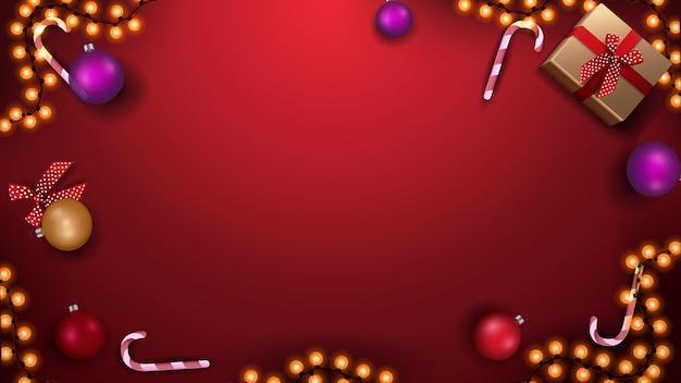 Modello per banner o cartolina di natale. modello rosso con palle di natale, bastoncini di zucchero, ghirlanda e regali, vista dall'alto Vettore Premium