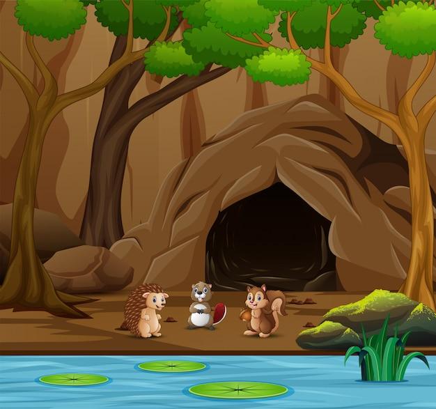 Molti animali cartoon vivono nella grotta Vettore Premium