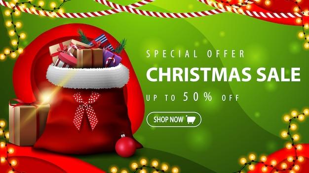 Offerta speciale, saldi natalizi, fino al 50% di sconto, banner sconto orizzontale verde in stile taglio carta con borsa babbo natale con regali Vettore Premium