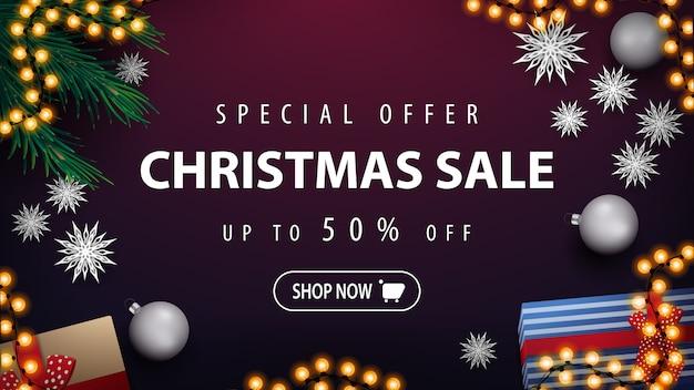 Offerta speciale, saldi natalizi, fino al 50% di sconto, banner sconto viola con ghirlanda, rami di alberi di natale, palline d'argento, regali e fiocchi di neve di carta, vista dall'alto Vettore Premium