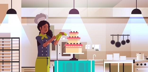 Pasticcere professionista femminile che decora la torta saporita della torta della crema dell'afroamericano in uniforme che cucina il ritratto moderno dell'interno della cucina di concetto dell'alimento di concetto dell'alimento Vettore Premium