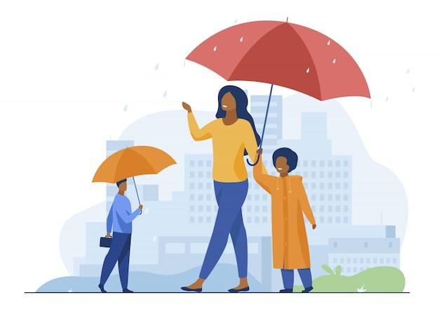 Persone che camminano durante la pioggia sulla strada Vettore gratuito