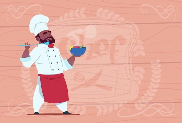 Piatto afroamericano della tenuta del cuoco del cuoco unico con il capo sorridente del fumetto della minestra calda in uniforme bianca del ristorante sopra fondo strutturato di legno Vettore Premium