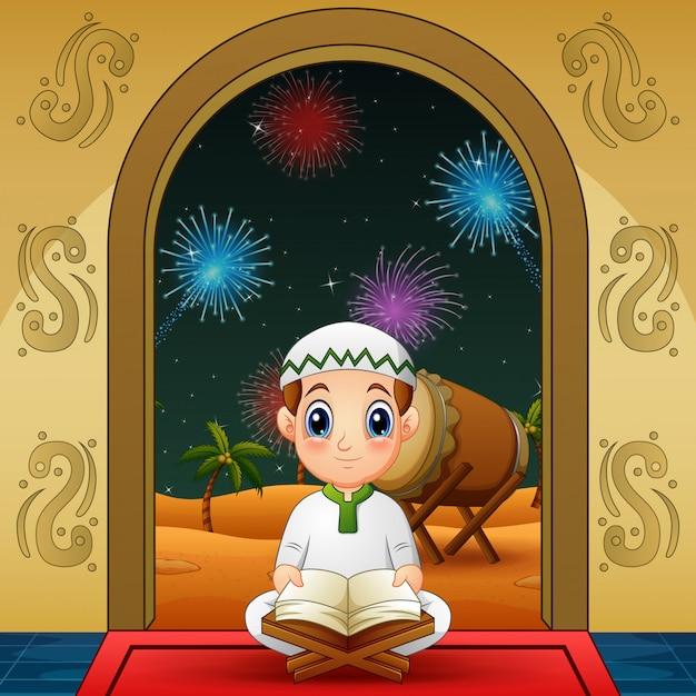 Piccolo ragazzo musulmano sveglio che legge corano alla notte Vettore Premium