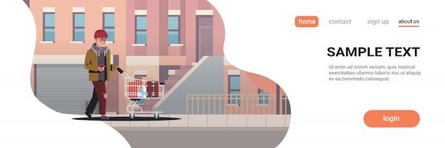 Poveretto che spinge carrello con effetti personali mendicante che cammina per strada chiedendo aiuto paesaggio urbano di edifici moderni senzatetto Vettore Premium