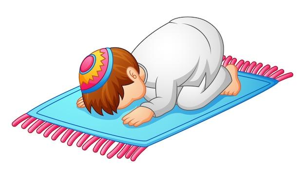 Prostrazione ragazzino per pregare di musulmano Vettore Premium