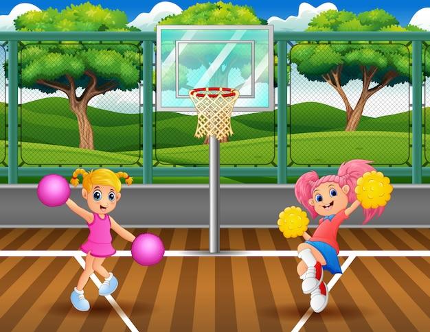 Ragazze pon pon che ballano sul campo da basket Vettore Premium