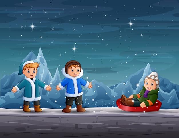 Ragazzi felici che giocano nella scena invernale Vettore Premium