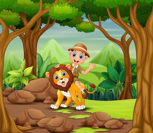 Ragazzo e leone felici dello zookeeper in una foresta Vettore Premium