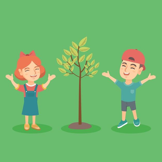 Ragazzo e ragazza caucasici felici che saltano vicino all'albero Vettore Premium