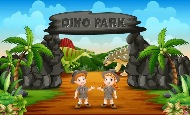 Ragazzo e ragazza del guardiano dello zoo sull'entrata del parco di dino Vettore Premium