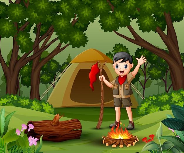 Ragazzo scout che si accampa nella foresta Vettore Premium