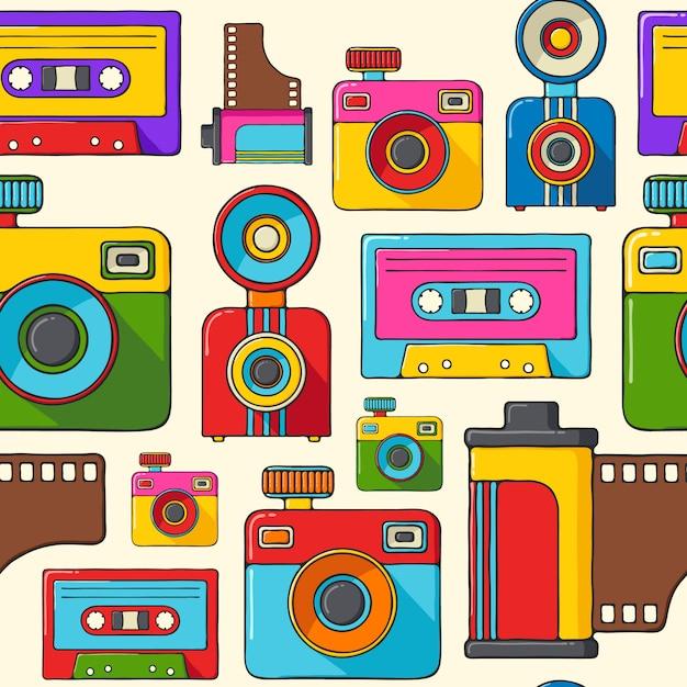 Retro macchine fotografiche e audiocassette disegnata a mano stile pop art senza cuciture. Vettore Premium
