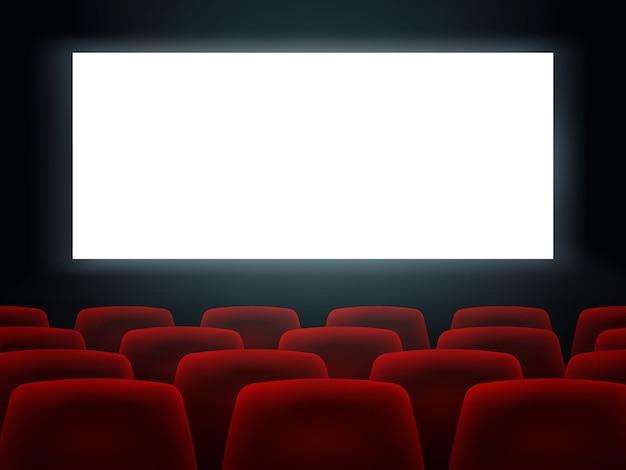 Sala cinema con schermo bianco vuoto e posti a sedere Vettore Premium