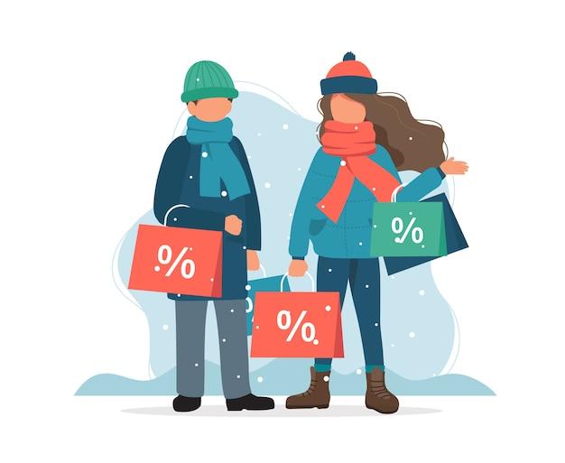 Saldi invernali, uomo e donna con borse della spesa in inverno. Vettore Premium