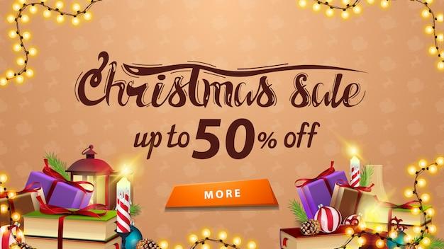 Saldi natalizi, fino al 50% di sconto, banner sconto beige con ghirlanda, bottone e tanti regali Vettore Premium