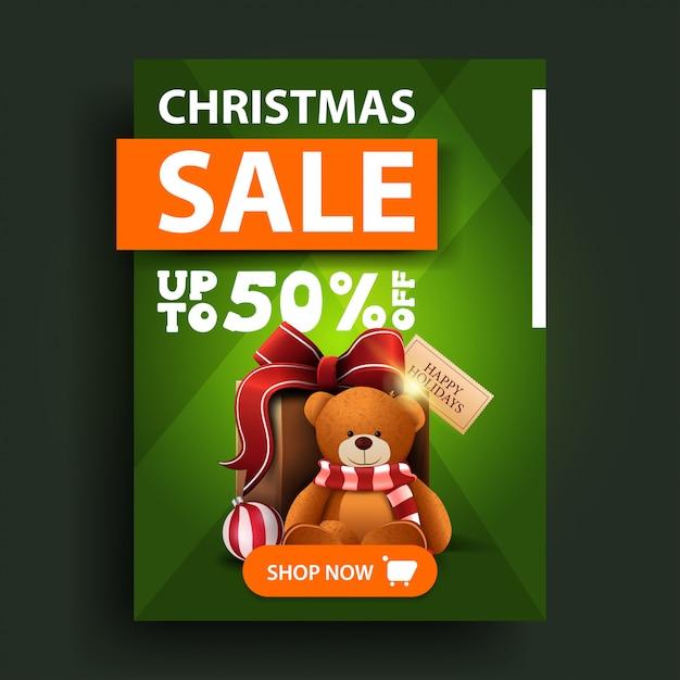 Saldi natalizi, fino al 50% di sconto, banner verde verticale con bottone e presente con orsacchiotto Vettore Premium