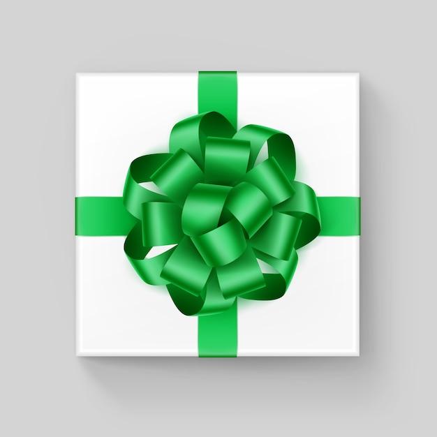 Scatola regalo quadrata bianca con fiocco in nastro verde smeraldo lucido vicino vista dall'alto isolato su sfondo Vettore Premium