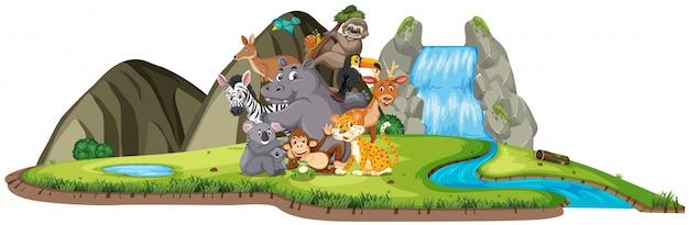 Scena con molti animali selvatici vicino alla cascata Vettore Premium