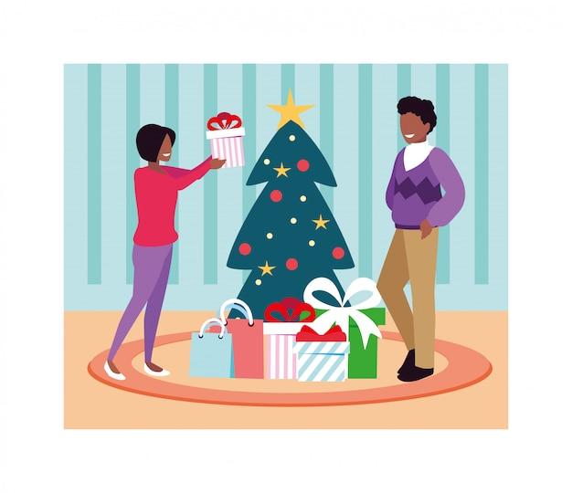 Scena delle coppie con l'albero di natale e il regalo Vettore Premium