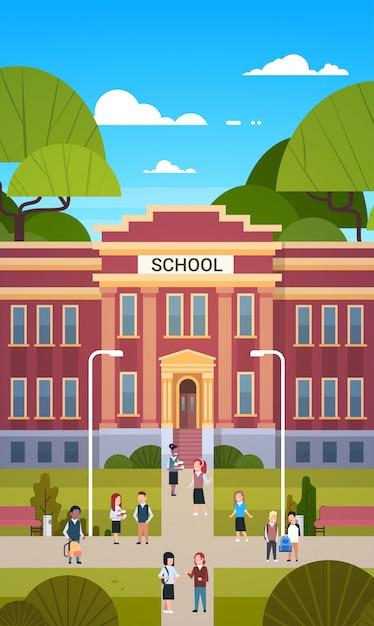Scolari che vanno a scuola edificio esterno con gruppo di alunni studenti Vettore Premium