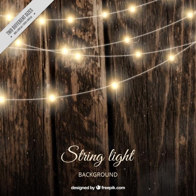 Sfondo di legno realistico con luci stringa Vettore gratuito