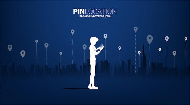 Siluetta dell'uomo con il cellulare e l'icona di gps con il fondo della città. concetto di posizione e luogo della struttura, tecnologia gps Vettore Premium