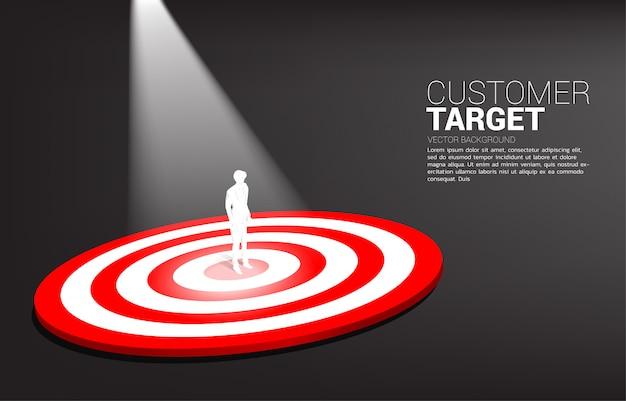 Siluetta dell'uomo d'affari che sta sul centro del bersaglio con la luce del punto. concetto di business dell'obiettivo e del cliente di marketing. missione e obiettivo della visione aziendale. Vettore Premium