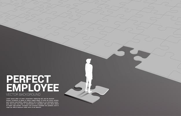 Siluetta dell'uomo d'affari che sta sul pezzo finale del puzzle. Vettore Premium