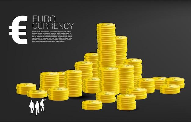 Siluetta della squadra che osserva in cima alla pila di moneta di valuta euro Vettore Premium