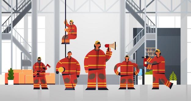Squadra di vigili del fuoco in piedi insieme vigili del fuoco indossando uniforme e casco antincendio concetto di servizio di emergenza moderna vigili del fuoco interni Vettore Premium