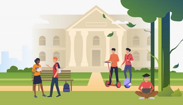 Studenti che camminano e chiacchierano nel parco del campus Vettore gratuito
