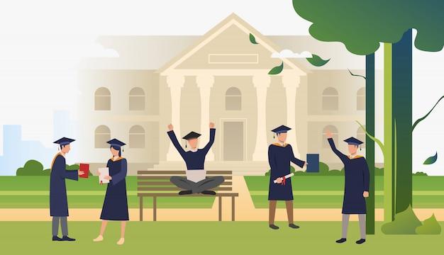 Studenti con diplomi che celebrano la laurea nel parco del campus Vettore gratuito
