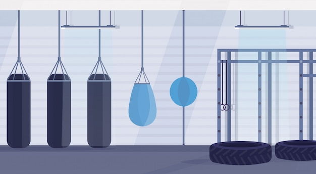 Studio di boxe vuoto con sacchi da boxe di diverse forme per praticare arti marziali in palestra moderna lotta club interior design orizzontale banner piatto Vettore Premium