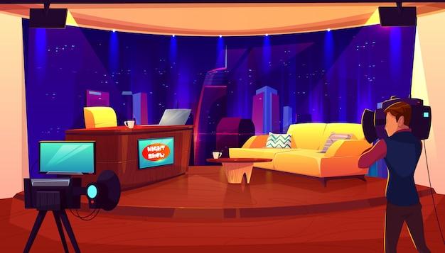 Studio televisivo con telecamera, luci, tavolo per giornalista, divano per interviste e programma televisivo di registrazione, spettacolo. Vettore gratuito