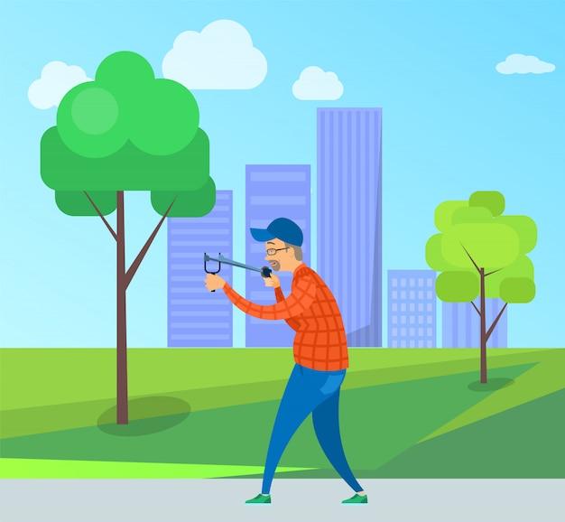 Targeting maschio invecchiato con catapulta nel parco Vettore Premium