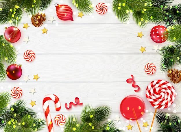 Tavolo in legno realistico sfondo incorniciato con rami di abete caramelle e decorazioni natalizie Vettore gratuito