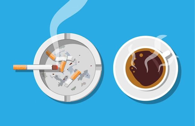 Tazza di caffè e posacenere pieno di sigarette fumi. Vettore Premium