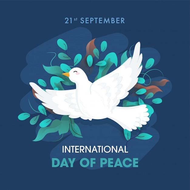 Testo della giornata internazionale della pace con colomba che vola e foglie di ulivo decorate su sfondo blu. Vettore Premium