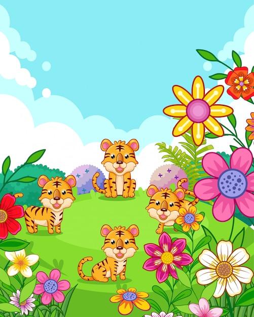 Tigri sveglie felici con i fiori che giocano nel giardino Vettore Premium